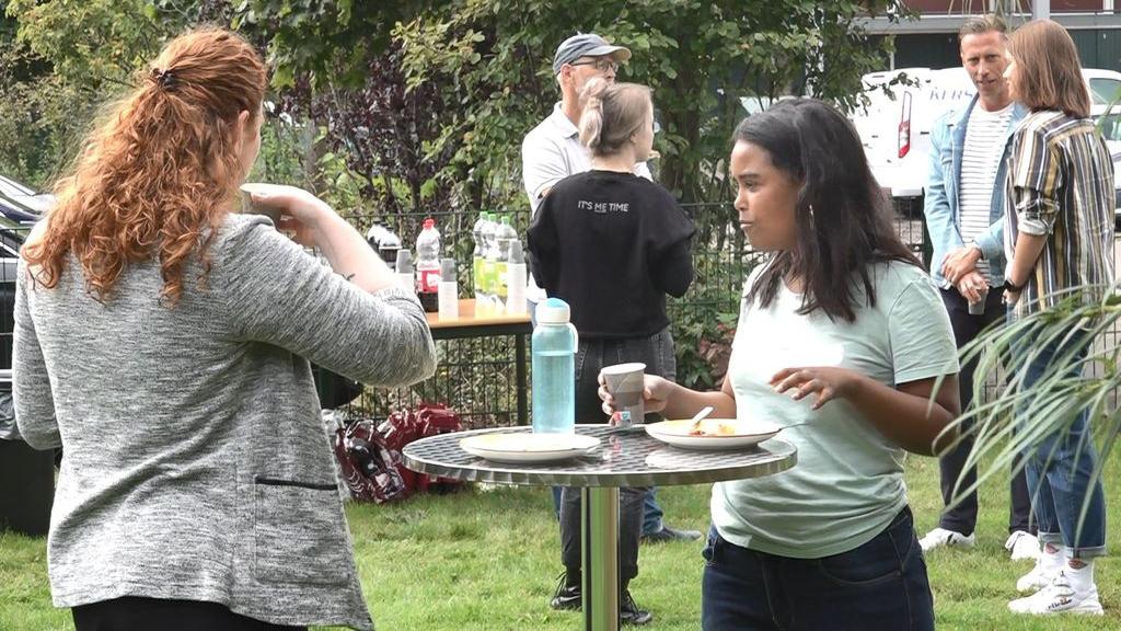 Buurtbewoners en kerkgangers praten met elkaar en genieten van de barbecue op het buurtfeest. Foto: Omroep Gelderland