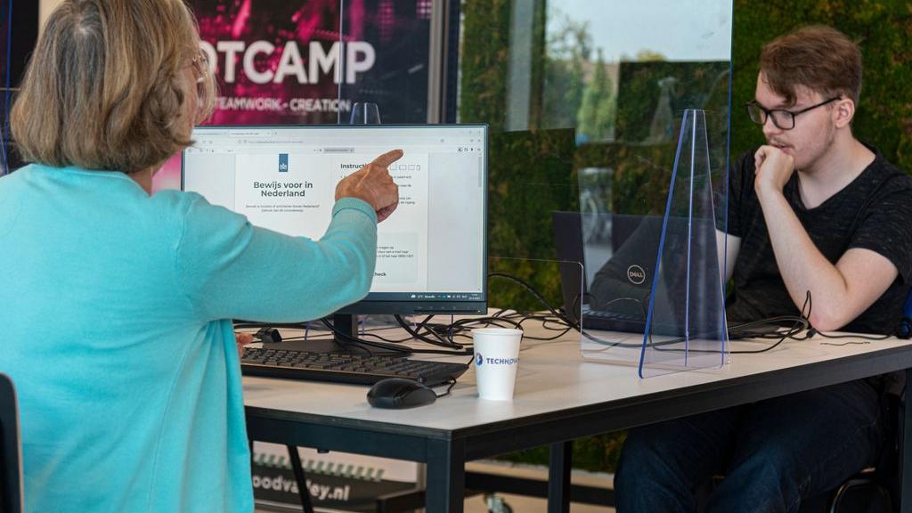 Studenten van het Technova College helpen ouderen met het genereren van de QR code voor coronatoegangsbewijs