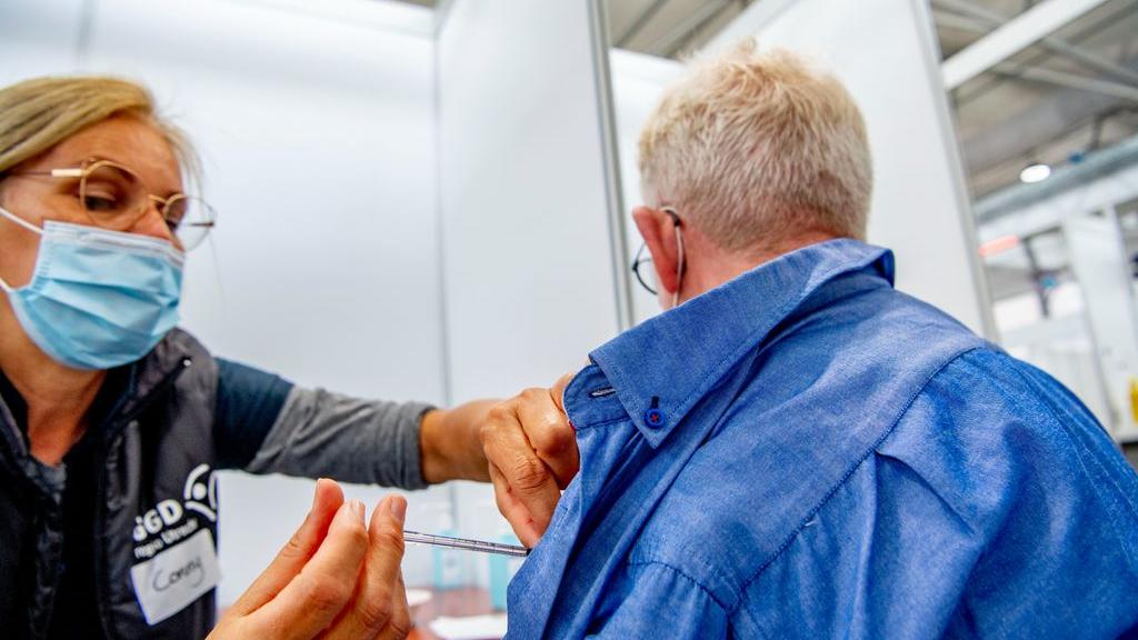 Een GGD-medewerker dient een vaccinatie toe tegen het coronavirus. Foto: ANP