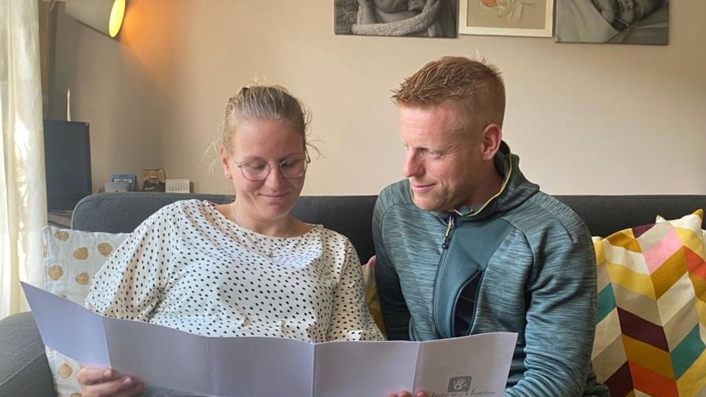 Regina en Geert-Jan bekijken de foto's die kort na zijn geboorte van Thijs zijn gemaakt. Aan de muur babyfoto's van hun dochters en in het midden een schilderij van hun doodgeboren zoon. Foto: Omroep
