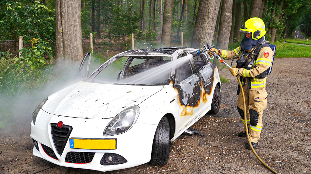 Auto brandt volledig uit op parkeerplaats bij het bos