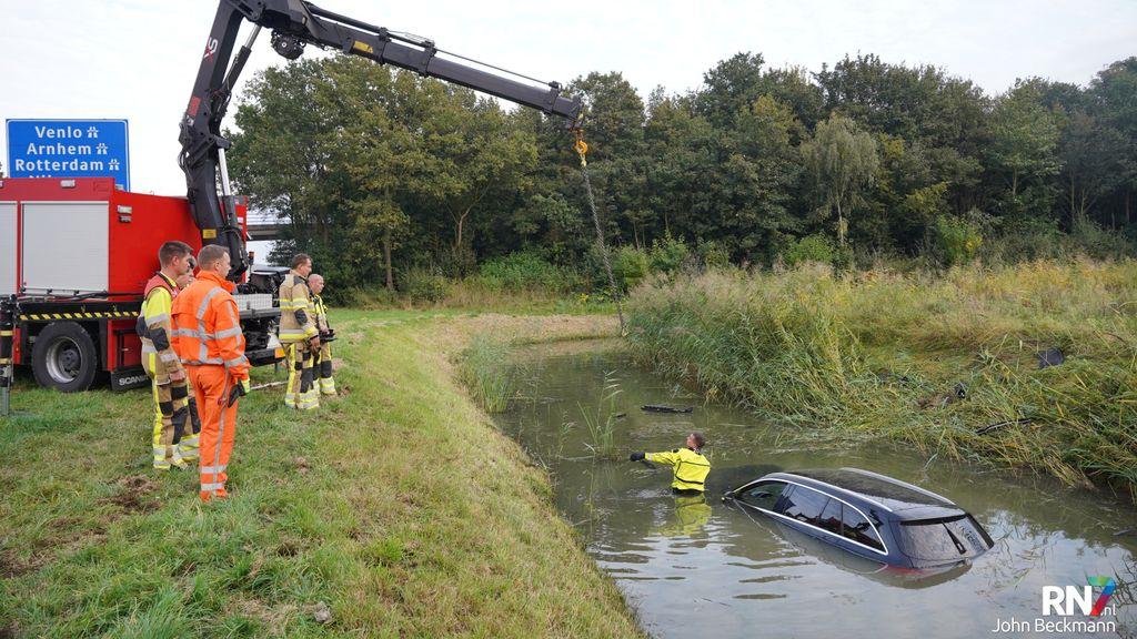 Auto te water in sloot naast snelweg A326 bij Wijchen