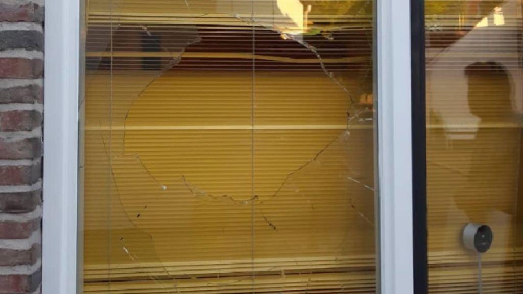 Steen door raam woning gegooid