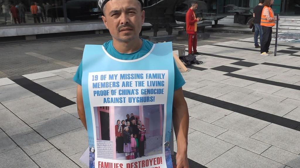 Oeigoer Abdurehim Gheni met foto's van zijn missende familieleden op zijn borst en rug. Foto: Omroep Gelderland